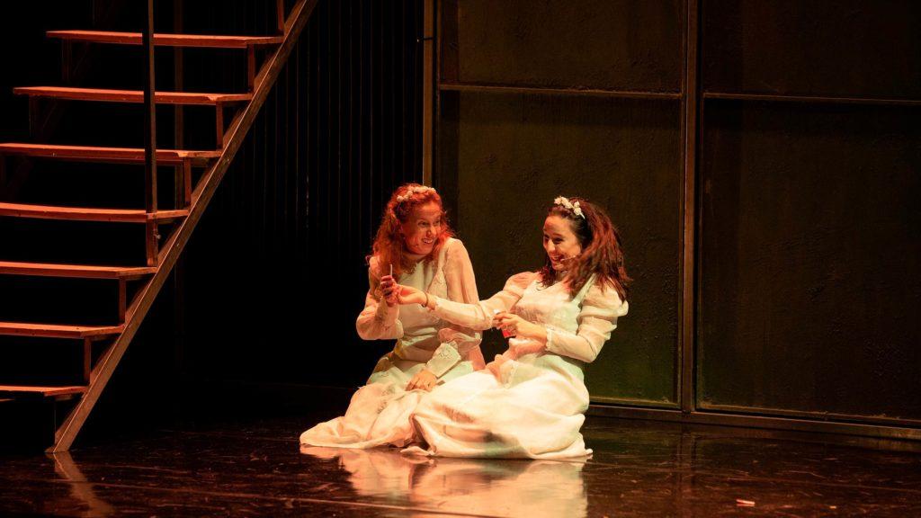 Cris Iglesias y María Vázquez, vestidas de blanco y riéndose en el escenario, en una escena de Fariña