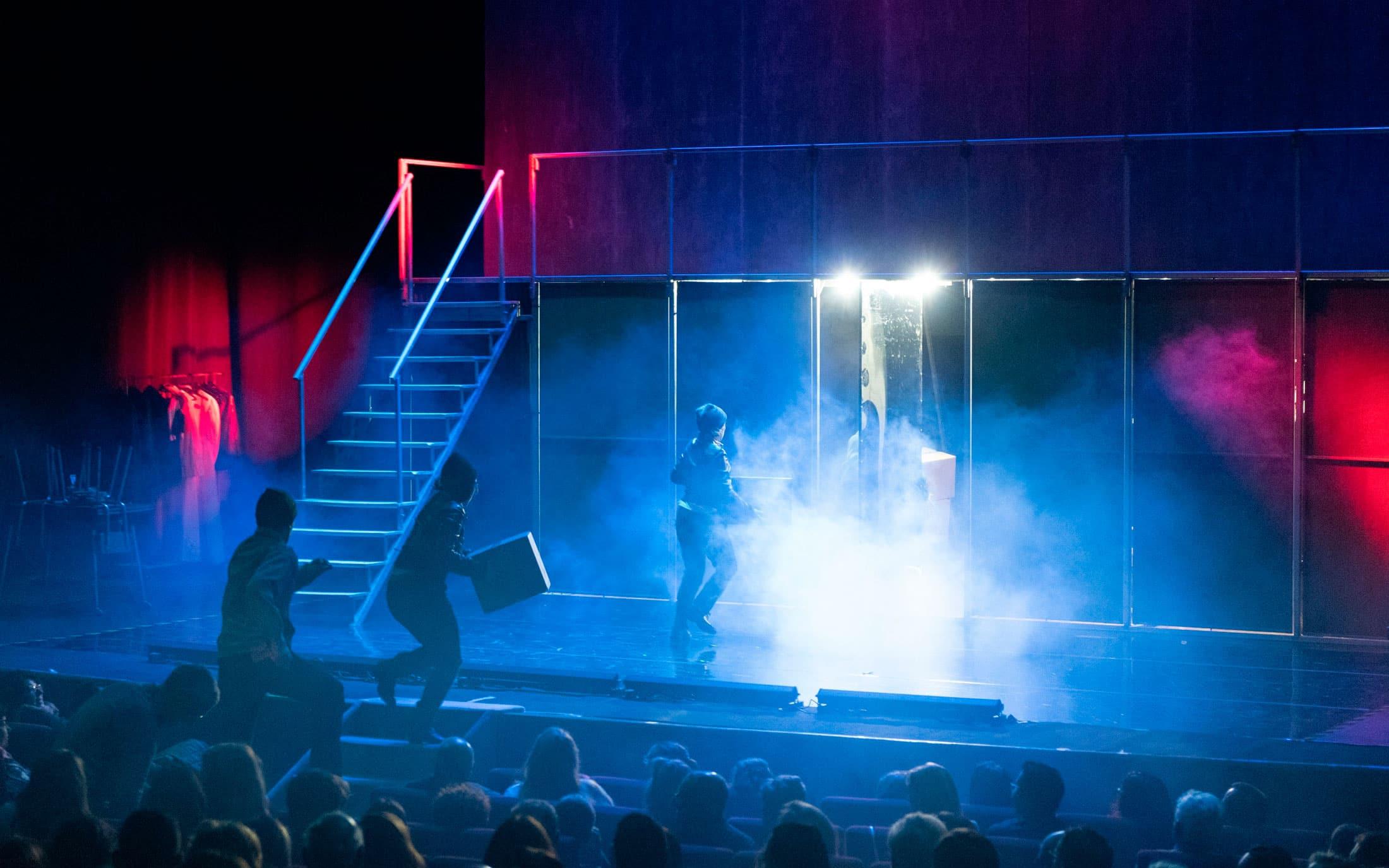 Hombres subiendo fardos de droga al escenario, durante una escena de la obra de teatro Fariña