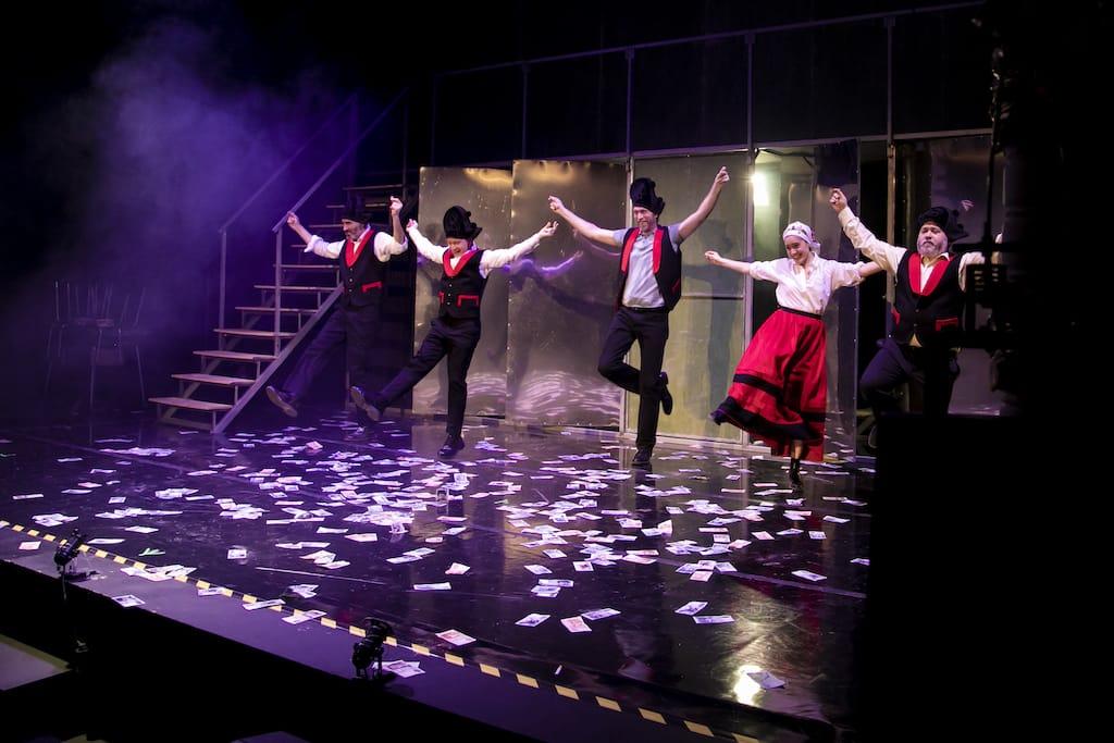 Los cinco actores de Fariña bailando sobre un escenario cubierto de billetes