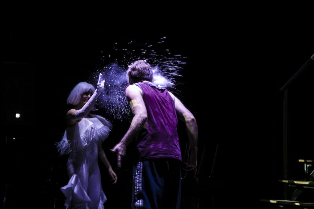 Melania Fernández tirando fariña a la cara de un actor durante el espectáculo