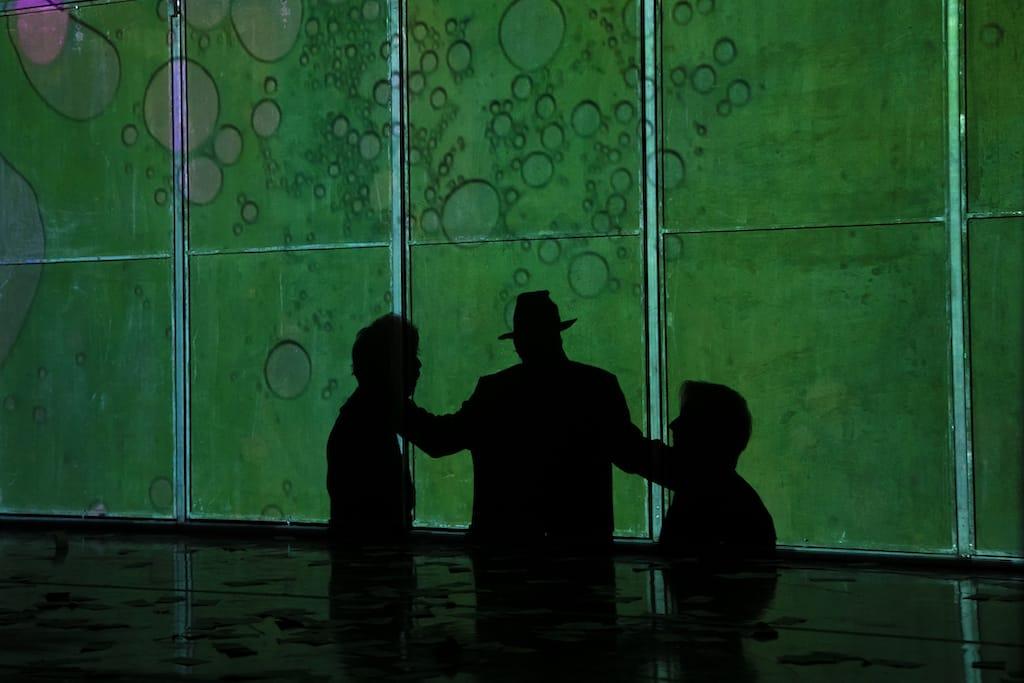 Siluetas de tres acortadas recortadas a contraluz sobre un fondo verde, un momento de la obra Fariña