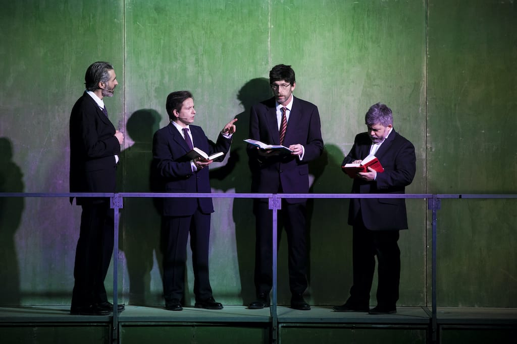 Víctor Duplá, Borja Fernández, Sergio Zearreta y Marcos Pereiro, vestidos de traje y ante una barandilla, durante la obra Fariña