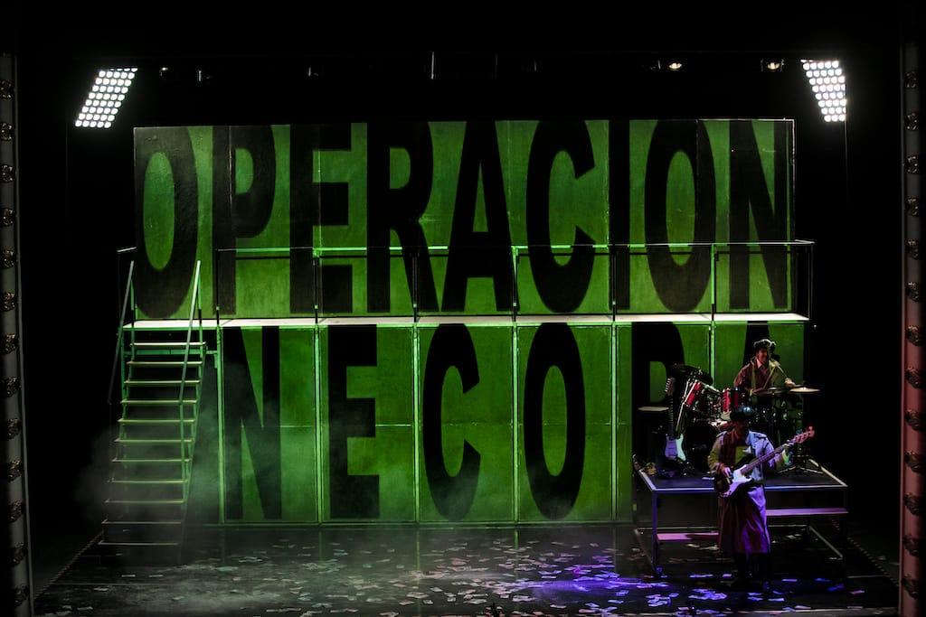 Dos actores de Fariña tocando la batería y la guitarra en el escenario. Sobre el fondo del escenario está impresa la frase Operación Nécora