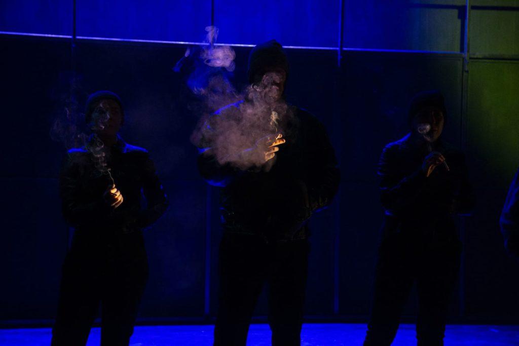 Tres persoas fumando en la penumbra, en una escena de la obra de teatro Fariña