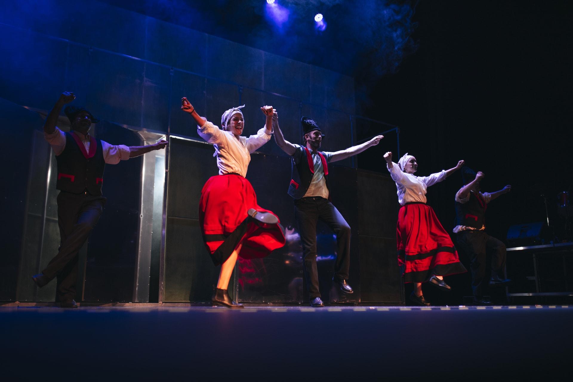 Los actores del espectáculo teatral Fariña bailando con trajes gallegos