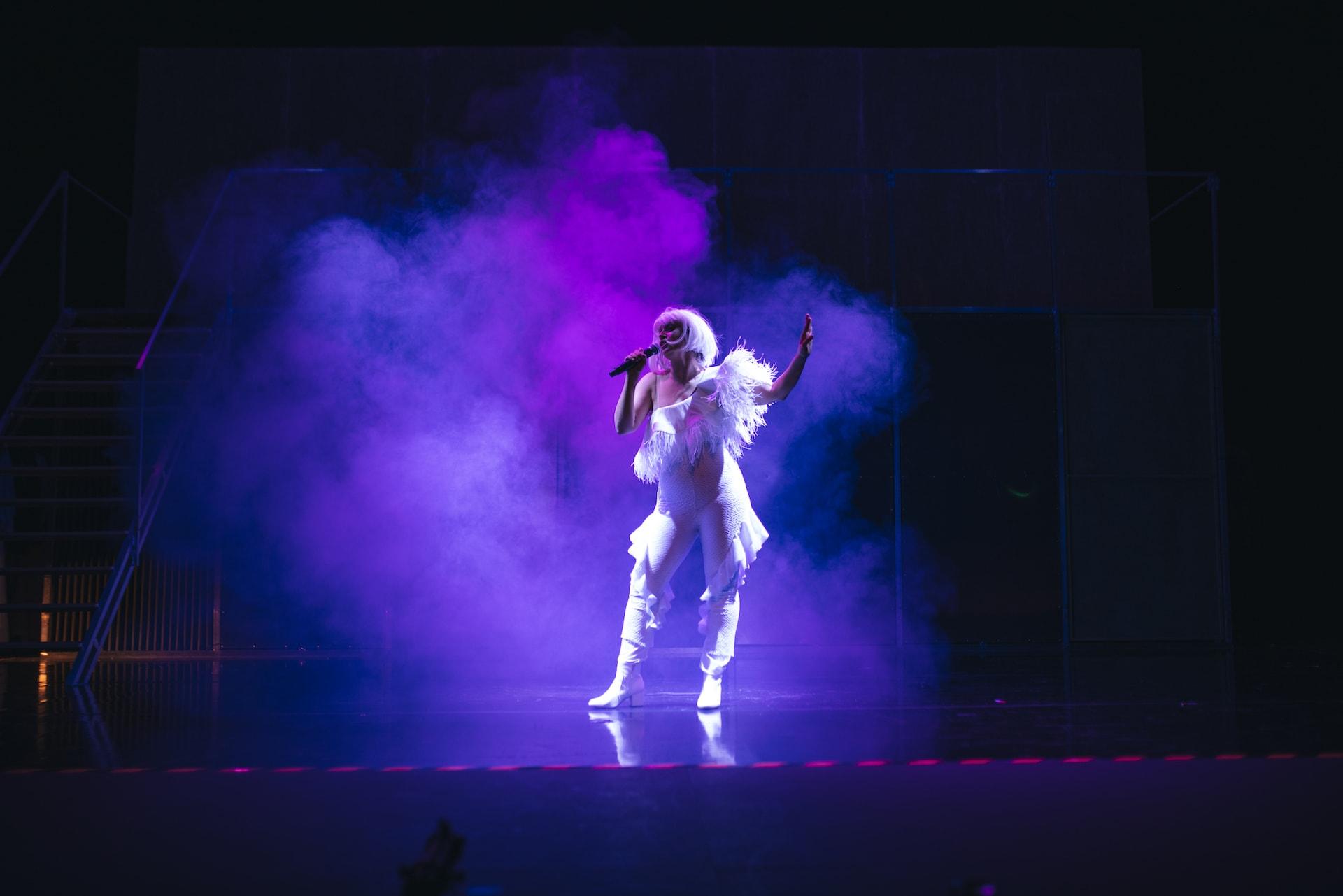 Graciela Carlos vestida de blanco y cantando durante la obra Fariña